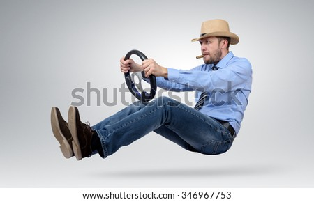 Funny bearded man in a hat and cigar driver car with a wheel, auto concept - stock photo