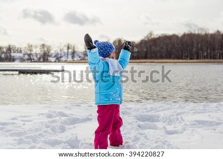 Funny beautiful little girl enjoying winter front of lake in sunny day. - stock photo