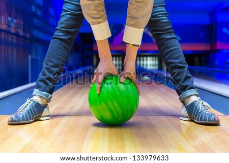 Funny beginner woman aiming to bowling pins - stock photo