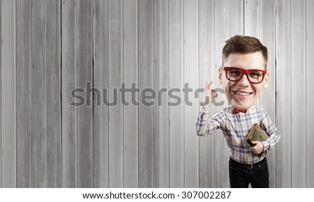 Funny big headed man in glasses with book in hands showing ok gesture - stock photo