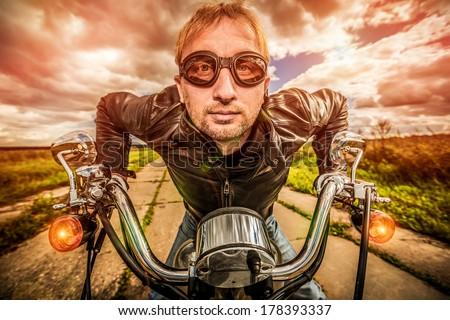 Funny Biker in sunglasses and leather jacket racing on the road (fisheye lens). Filter applied in post-production. - stock photo