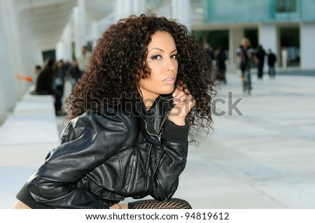 Funny black female model at fashion sitting on a bench - stock photo