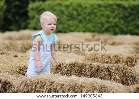 Funny blond baby girl is walking thought a hay labyrinth in a farm during halloween activity - stock photo