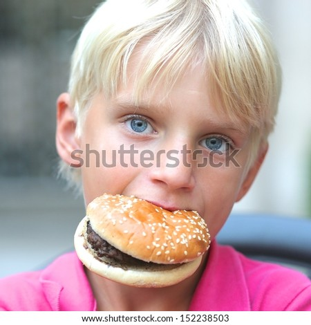 Funny blond boy with beautiful blue eyes holding in his mouth tasty hamburger - stock photo