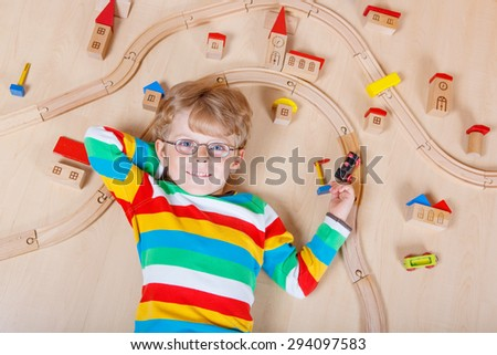 Funny blond child in glasses playing wooden trains and railroad indoor. Active kid boy wearing colorful shirt and having fun with building and creating. - stock photo