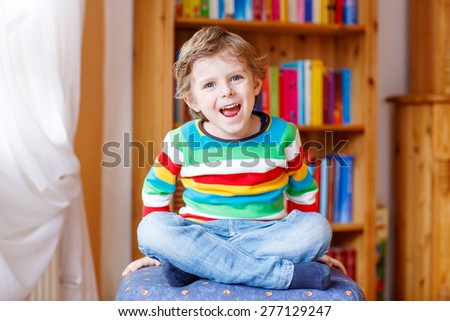Funny blond kid boy having fun and smiling, indoors. Child wearing colorful shirt. Portrait in a daycare. - stock photo