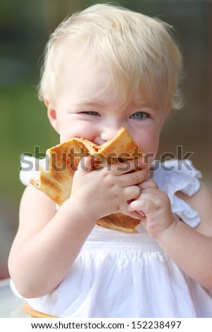 Funny blond little baby girl in beautiful white dress biting on piece of tasty pizza holding it with two hands - stock photo