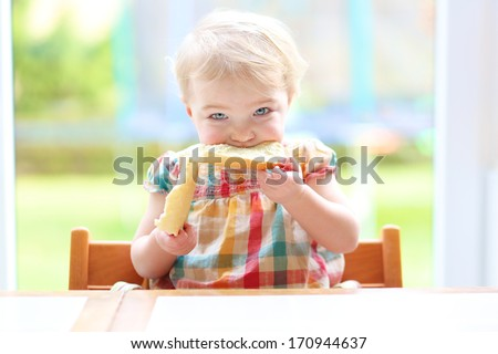 Funny blonde toddler girl eating tasty bread with butter sitting in the kitchen nearby big window with garden view - stock photo