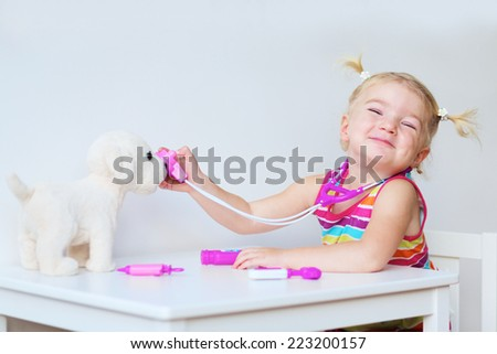 Funny blonde toddler girl playing doctor role game examinating her puppy using stethoscope sitting at small white table in playroom at home, school or kindergarten - stock photo
