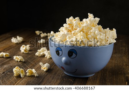 Funny bowl of popcorn on wooden table - stock photo