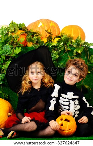 Funny boy and a girl wearing halloween costumes posing with pumpkins. Halloween. - stock photo