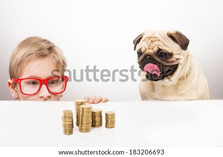 Funny boy and his dog looking over the desk at piles of coins   - stock photo
