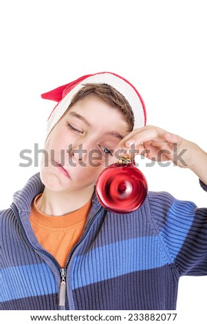 funny boy looking at a red christmas ball, isolated on white - stock photo
