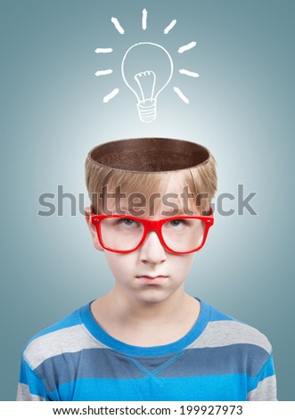 Funny boy looking at camera with a drawn electric bulb under his opened head. Concept - stock photo