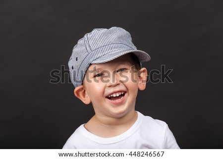 Funny boy with hat laughing.  Studio shot - stock photo