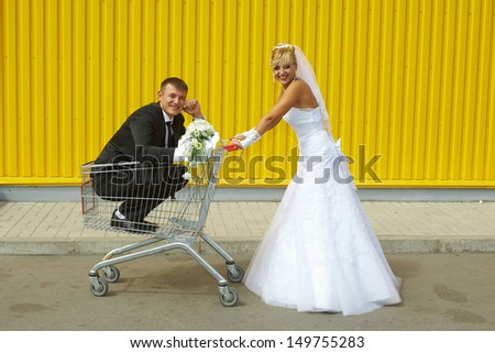 funny bride and groom playing with a basket of supermarket - stock photo