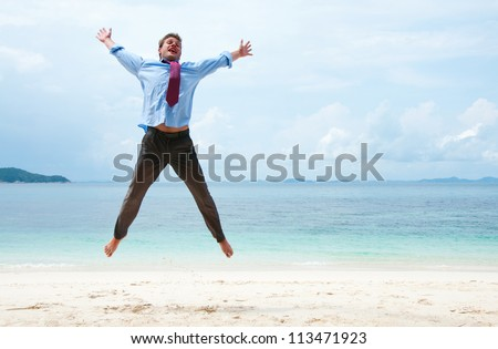 Funny business man jumping on the beach - stock photo