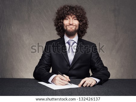 funny businessman holding a pen writing on a blank paper and smiling on grunge background - stock photo
