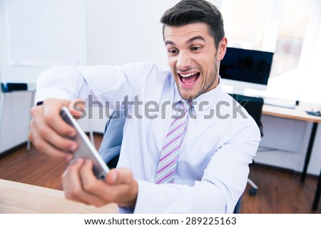 Funny businessman playing in game on the phone in office - stock photo