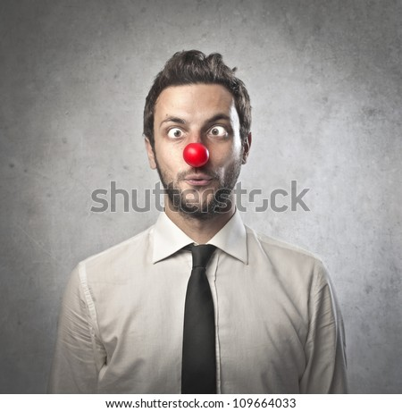 Funny businessman with red plastic nose - stock photo