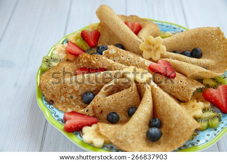 Funny butterfly shaped crepes with berries for kids - stock photo