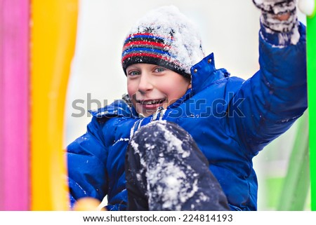 Funny cheerful boy in jacket and hat playing outdoors in winter sliding - stock photo