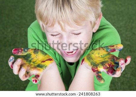 Funny child boy with hands painted with colorful paint - stock photo