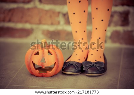 Funny child dressed witch costume holding pumpkin. Halloween holidays concept - stock photo