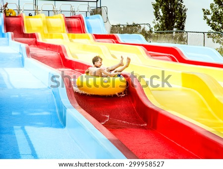 Funny child enjoying summer vacation in water park taking a ride on a float  - stock photo