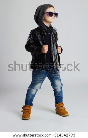 Funny child.fashionable little boy in sunglasses.stylish kid in yellow shoes.winter fashion children - stock photo