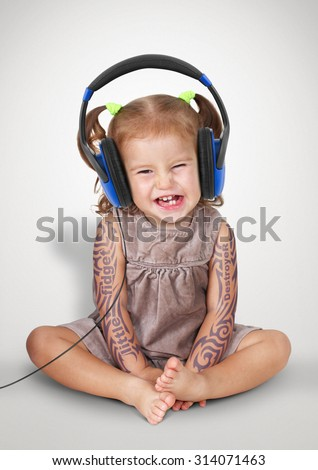 Funny child girl with tatoo listening music in headphones - stock photo