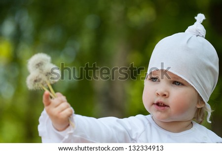 Funny child holding white dandelion - stock photo