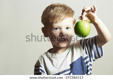 Funny Child holds the apple.Little Handsome Boy with green apple. Health food. Fruits. Enjoy Meal. 4 years old - stock photo