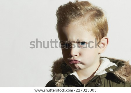 funny child in winter coat.little boy.hairstyle.emotion - stock photo