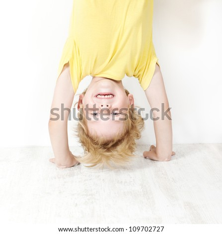 Funny child standing head over heels. Close up portrait - stock photo