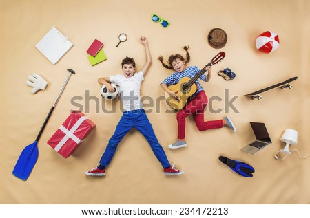 Funny children are playing together. Lying on the floor with guitar and ball - stock photo