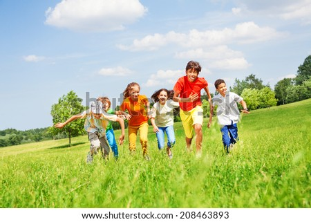 Funny children running in the field - stock photo