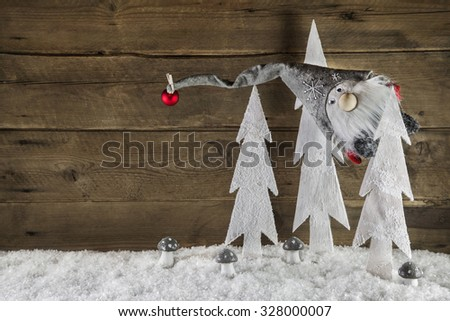 Funny christmas background of wood with snow and a santa hanging in a tree. - stock photo