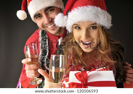 Funny Christmas couple with glasses of champagne  covering dark background - stock photo