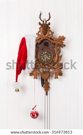 Funny christmas decoration with an old cuckoo clock and a red white santa hat. - stock photo