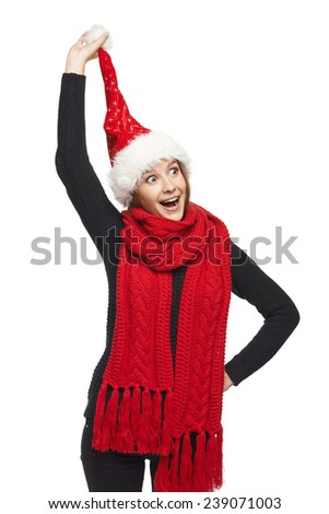 Funny Christmas woman surprised wearing Santa hat pulling her Santa hat pompon, looking at camera with mouth open in amazement - stock photo