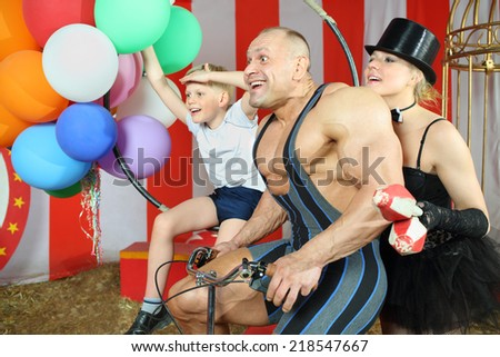 Funny circus family riding on retro bike with balloons in striped tent - stock photo