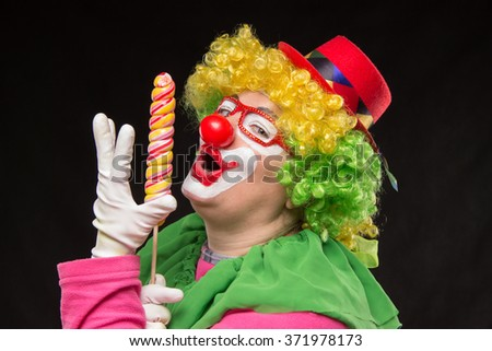 Funny clown in a hat with a big candy - stock photo