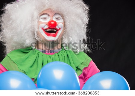 Funny clown with shaggy hair and a cheerful make-up holding a gift - stock photo
