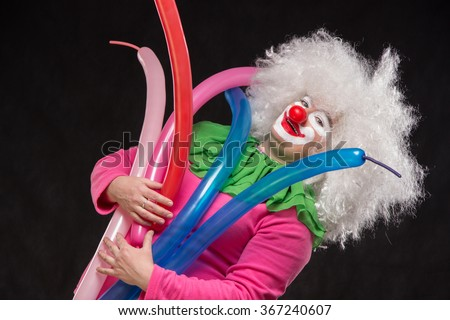 Funny clown with shaggy hair holding colorful balloons - stock photo