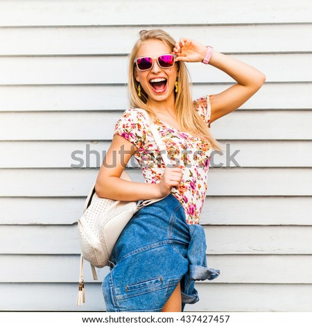 Funny cool cute beautiful hipster blonde girl posing against a white wall, bright casual wear, denim shirt, T-shirt, sunglasses, backpack, urban style, laughs, a broad smile, crazy emotions, joy - stock photo