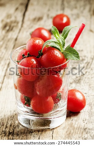 Funny cool tomato juice and tomatoes in a glass, selective focus - stock photo