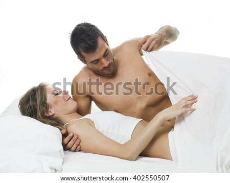 funny couple foreplaying in a white bed and sheets - stock photo