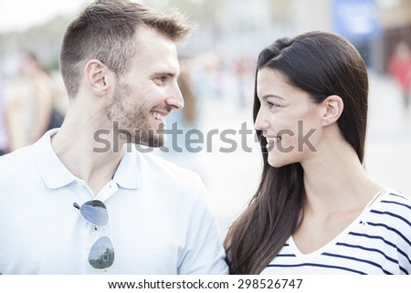 Funny couple laughing with a white perfect smile and looking each other outdoors with unfocused background - stock photo