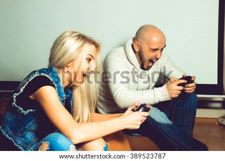 Funny couple playing computer games. concept of leisure entertainment and fun - stock photo